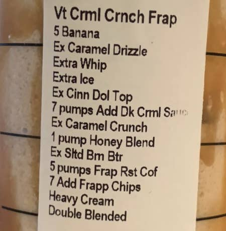 "A closeup of the order label, which includes modifications like ""add five bananas, extra caramel drizzle, extra whip, extra cinnamon dolce toping, heavy cream, double blended, and more."