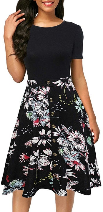 A model wearing the short sleeve dress with a bodice that looks like a black T-shirt and a button-front black and colorful floral skirt