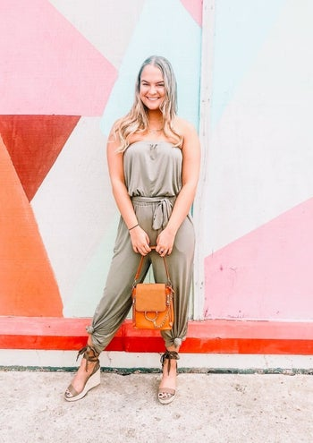 front view of a reviewer wearing the jumpsuit in taupe with the legs tied in a knot