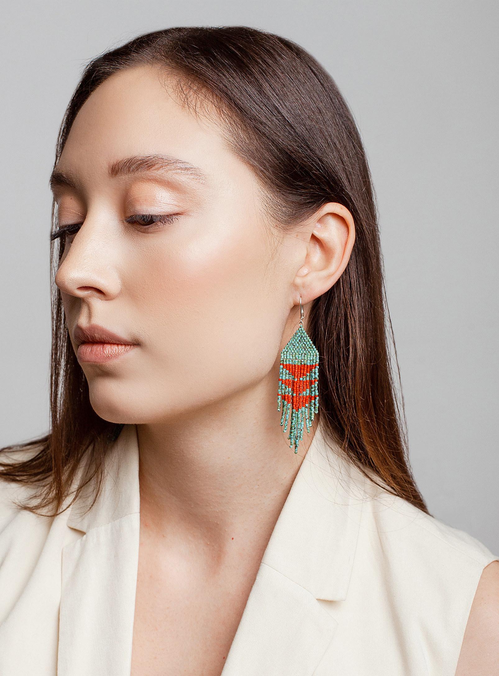 A person wearing long beaded earrings
