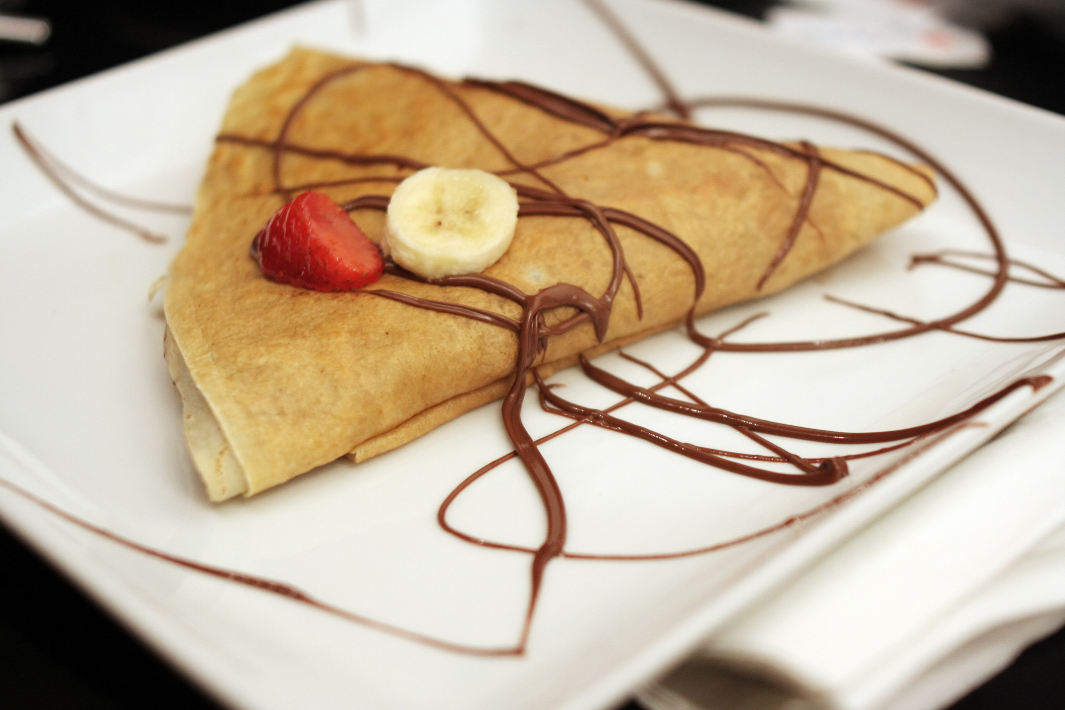 A crepe drizzled with chocolate and topped with a strawberry and a banana slice