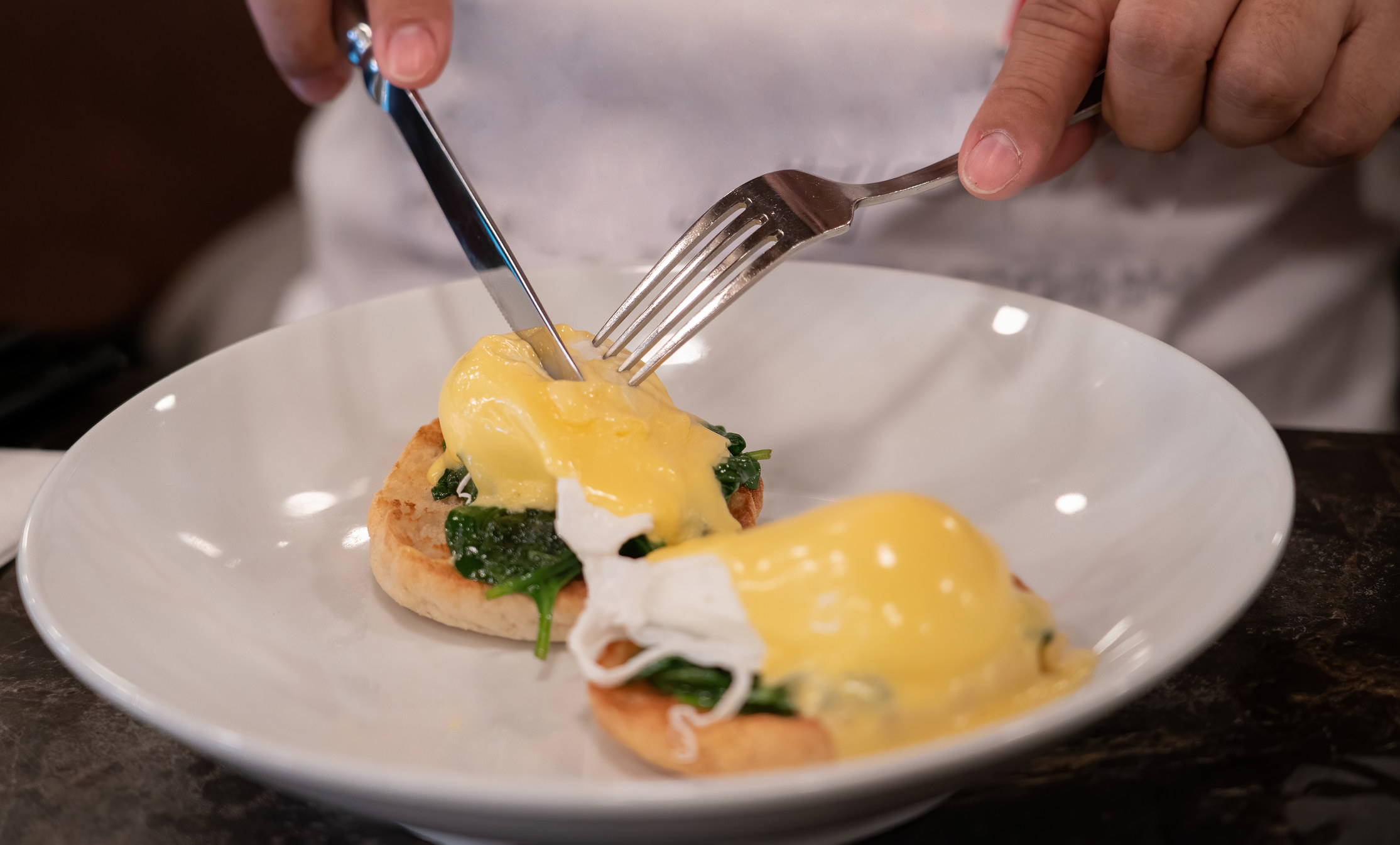 Someone cutting into a poached egg with hollandaise sauce