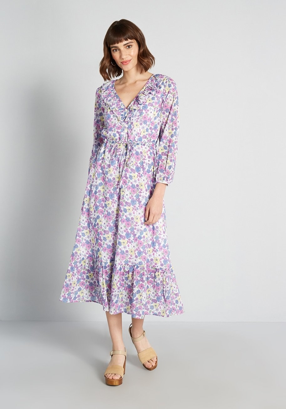 model in bracelet-sleeve purple, yellow, and white floral midi dress with ruffle details