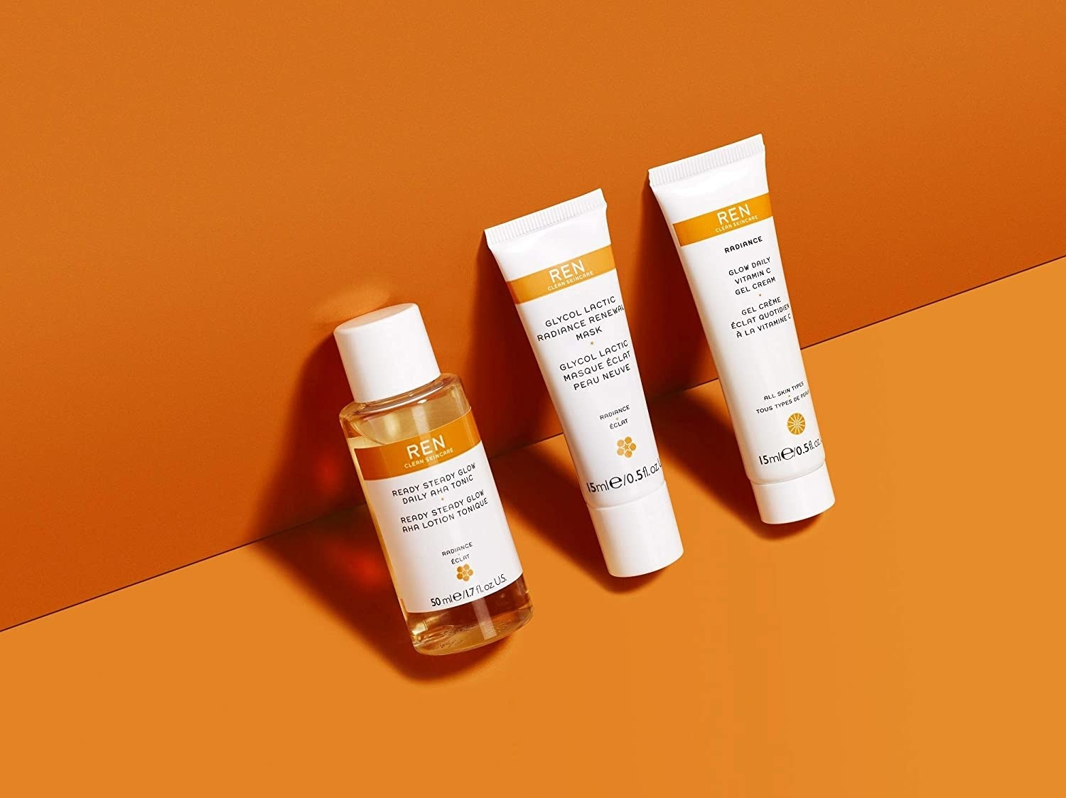 the three products resting against an orange wall