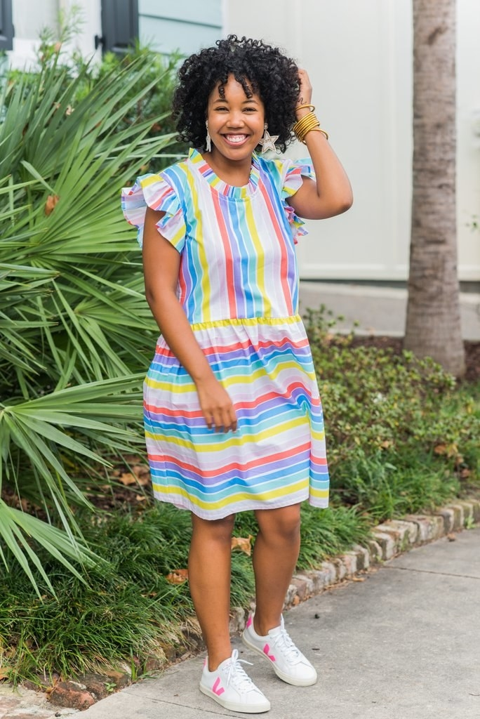 business owner wearing the rainbow stripe knee-length dress with short ruffle sleeves and ruffled neckline