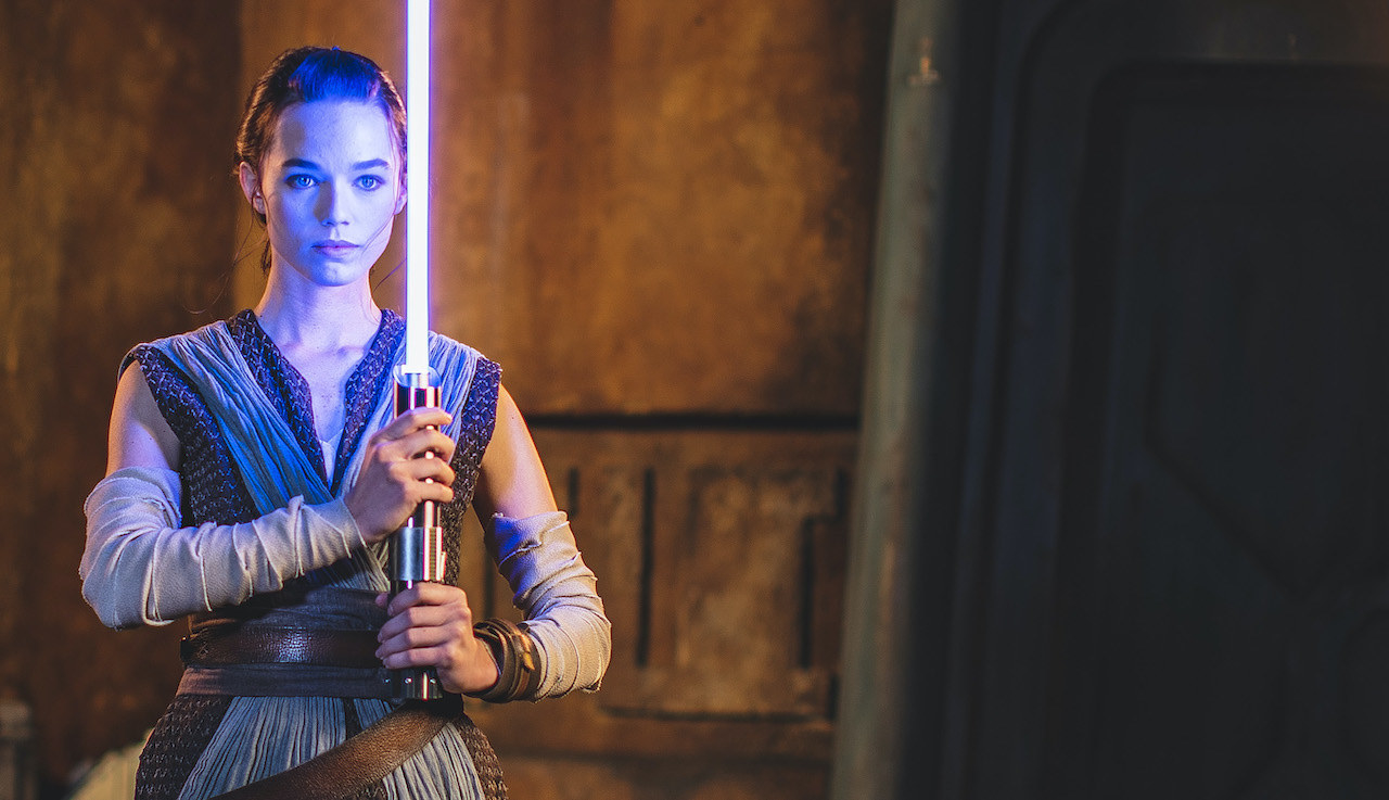 An actor dressed as Rey holding the new lightsaber