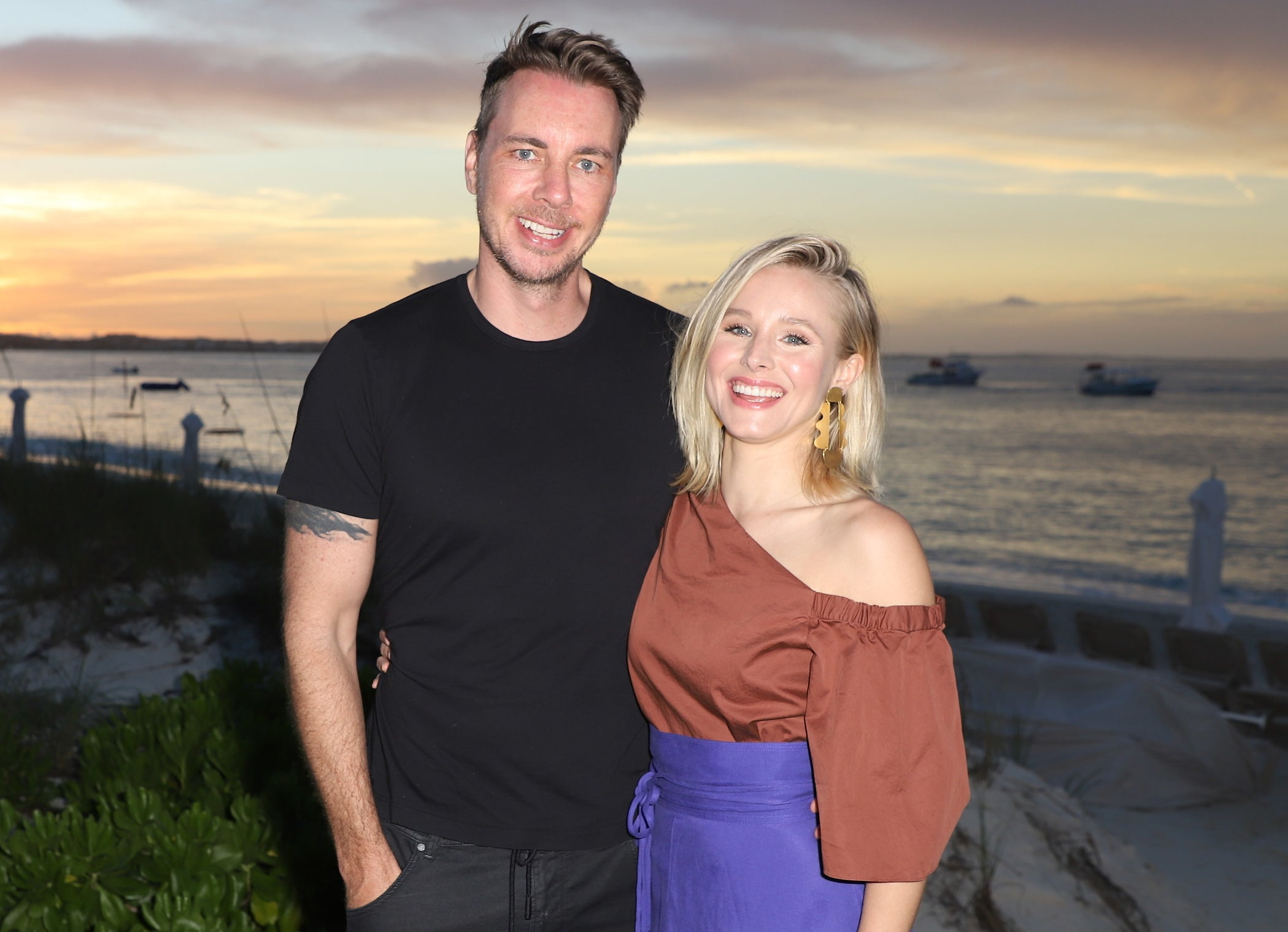 Dax and Kristen smile in front of a beach during sunset