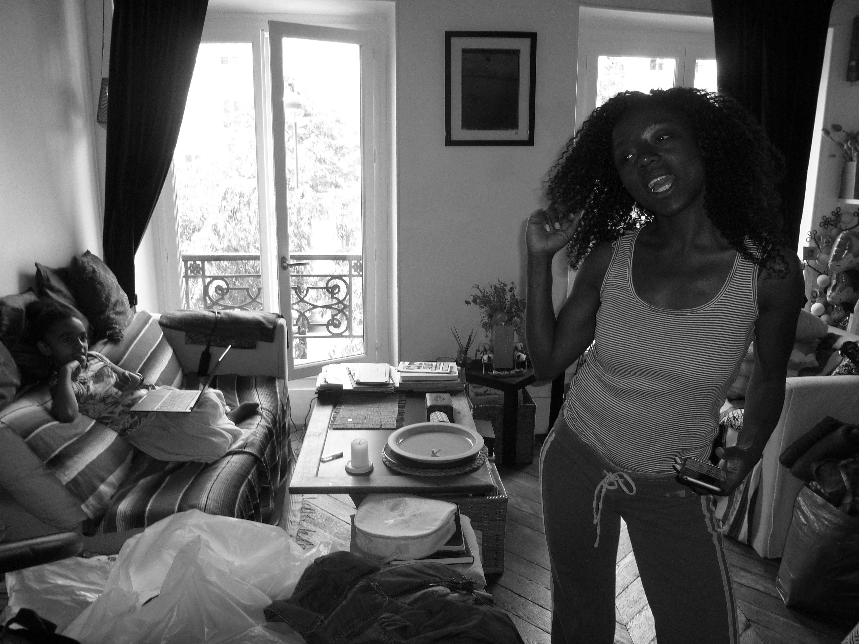 A woman stands in her apartment while her young daughter watches