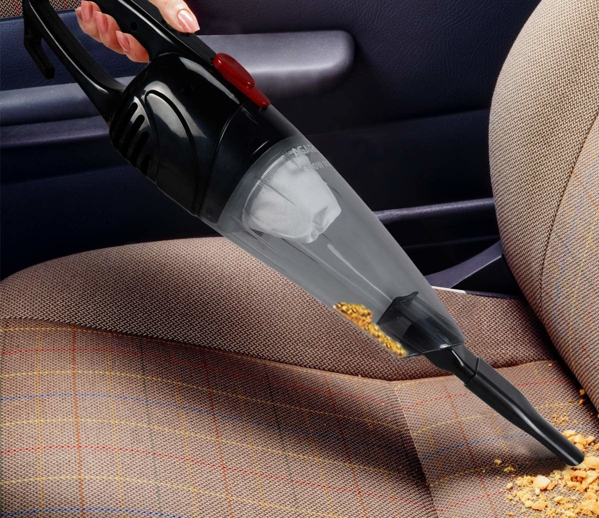 The handheld vacuum cleaner used to clean up crumbs from a car seat.