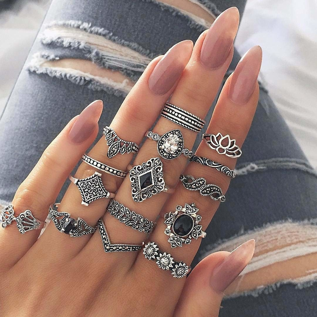 A person wearing oxidised metal rings of varying styles.