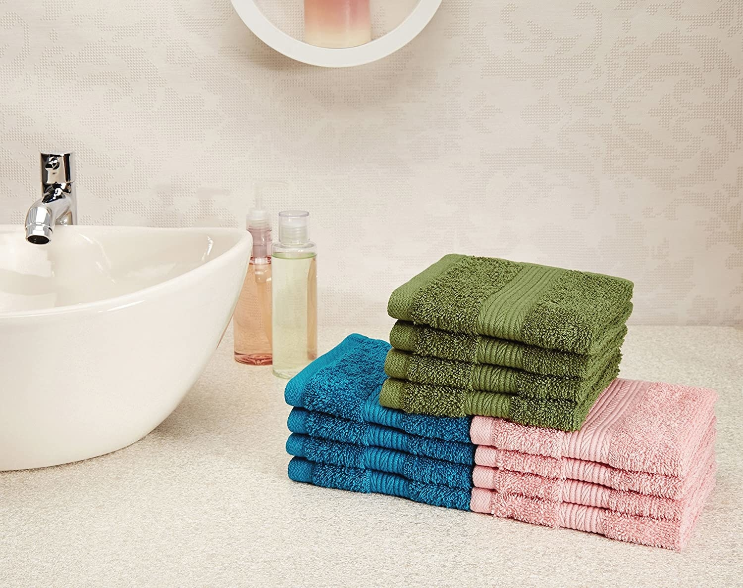 Pink, blue, and green hand towels stacked up next to a washbasin.