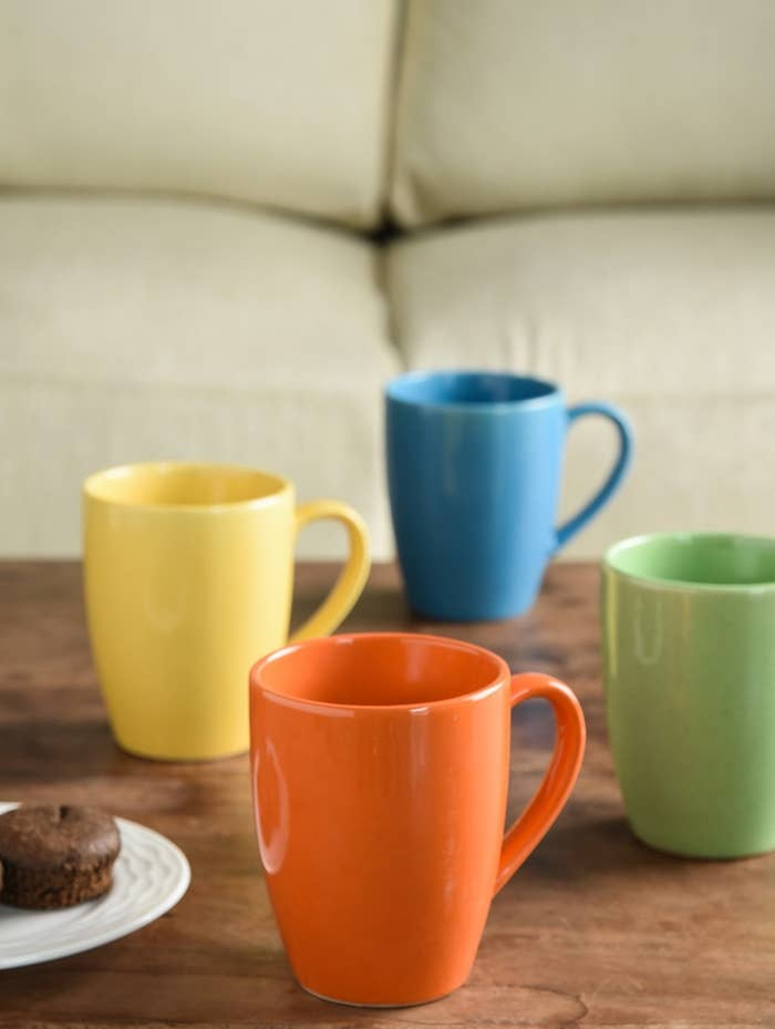 Orange, yellow, blue, and green mugs kept next to a plate of muffins.