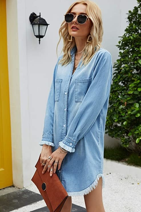 model wearing denim dress buttoned up with tons of accessories to dress it up