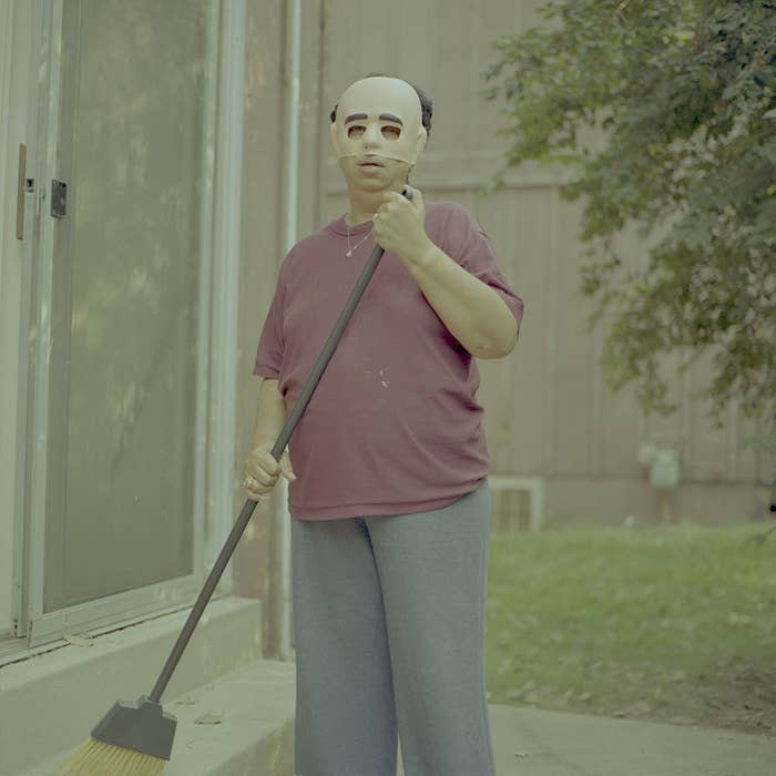 woman holds a broom while wearing a plastic mask