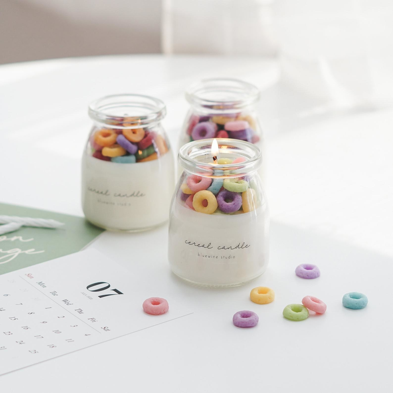 """A small milk jar-shaped glass candle with wax rainbow """"cereal"""" pieces on the top to look like Fruit Loops"""