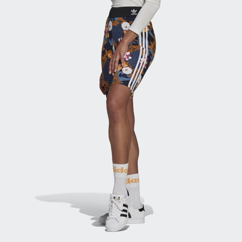 A model in patterned bike shorts with adidas waistband, socks, and sneakers