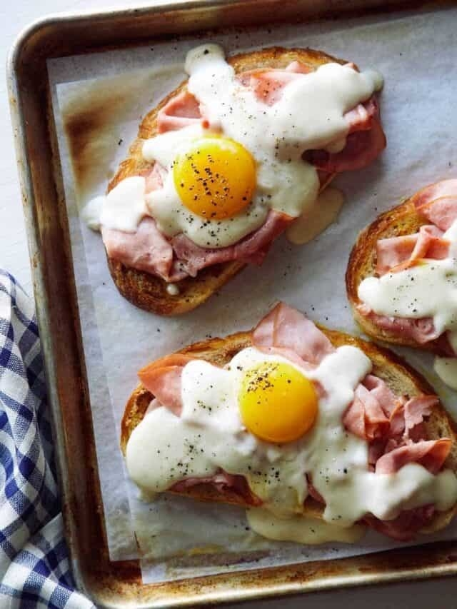 A sheet pan of Croque madame toasts with ham and cheese sauce and egg.