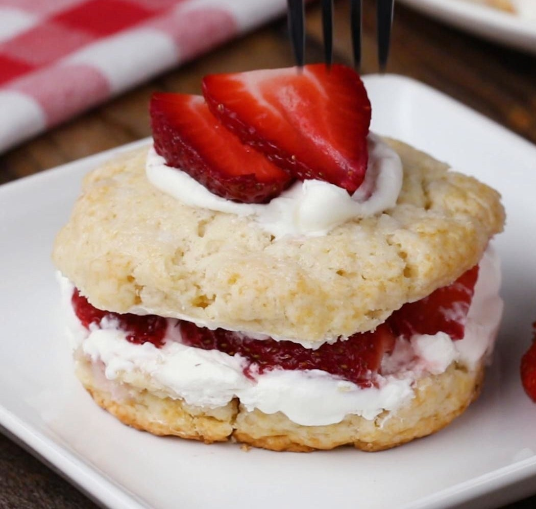 A slice of strawberry shortcake with fresh strawberry topping.