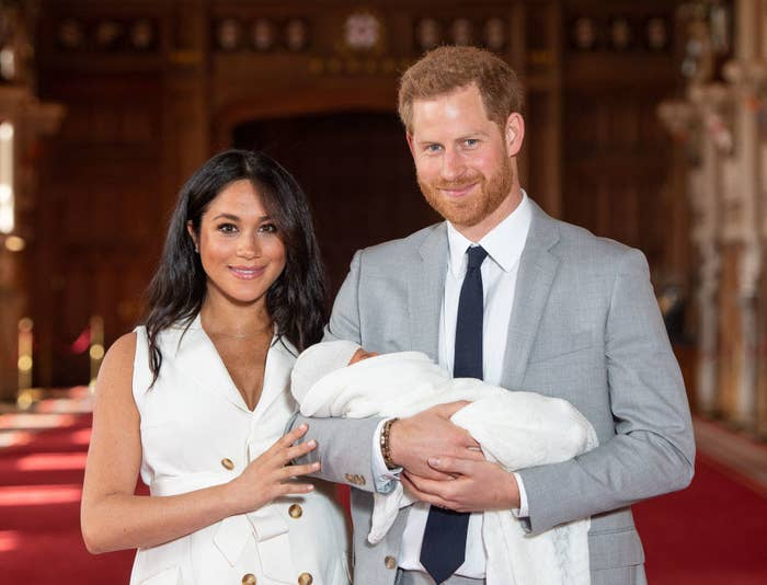 Prince Harry (R) and Meghan Markle pose with their newborn son, Archie during a photocall in St George's Hall at Windsor Castle