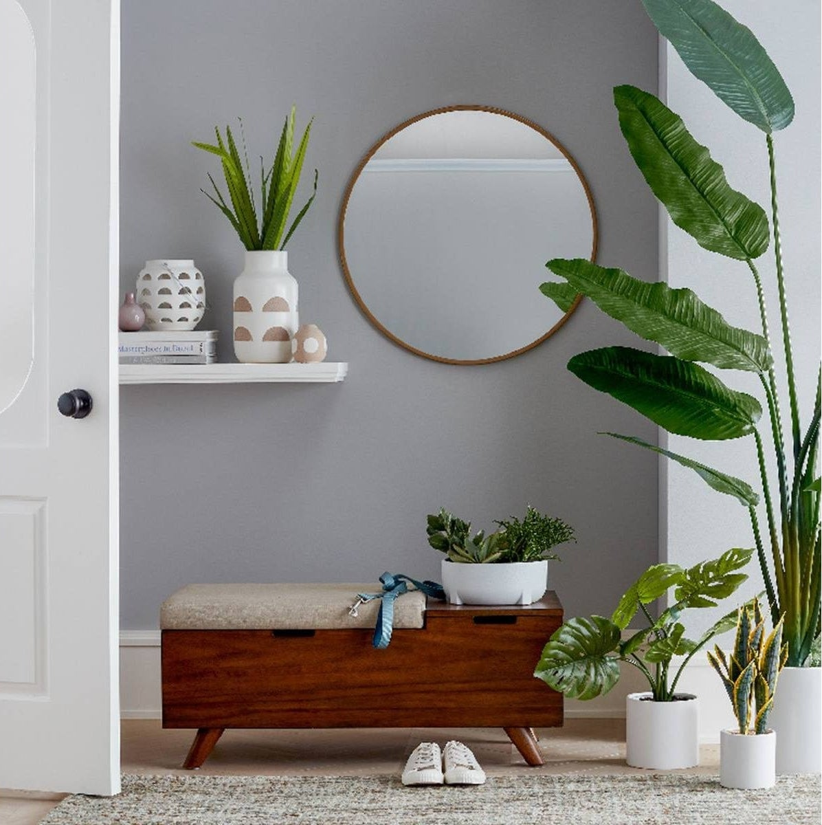 round mirror with gold frame hanging on a wall surrounded by plants