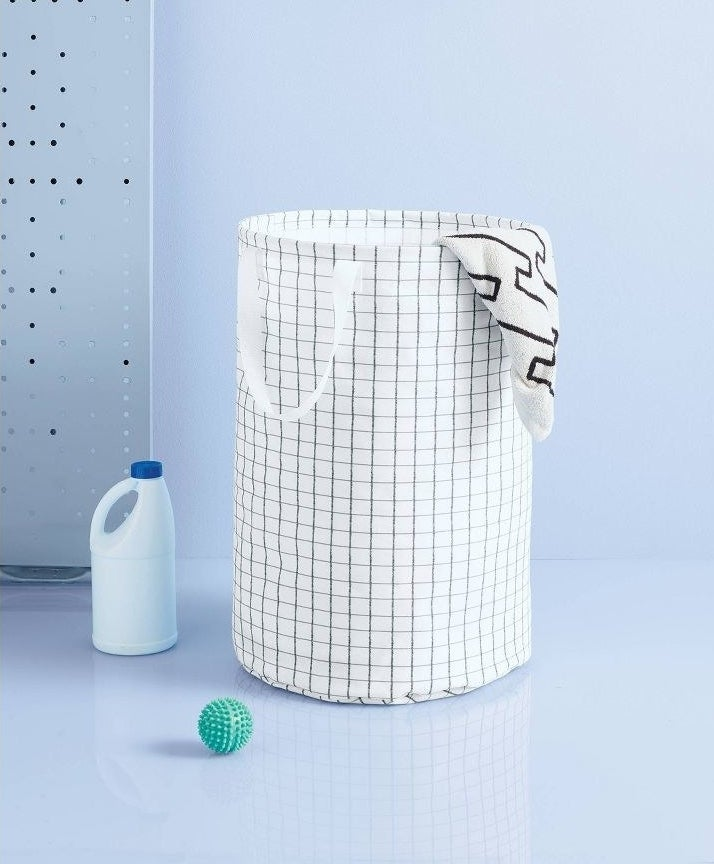 white and black cylindrical laundry hamper with handles and grid pattern