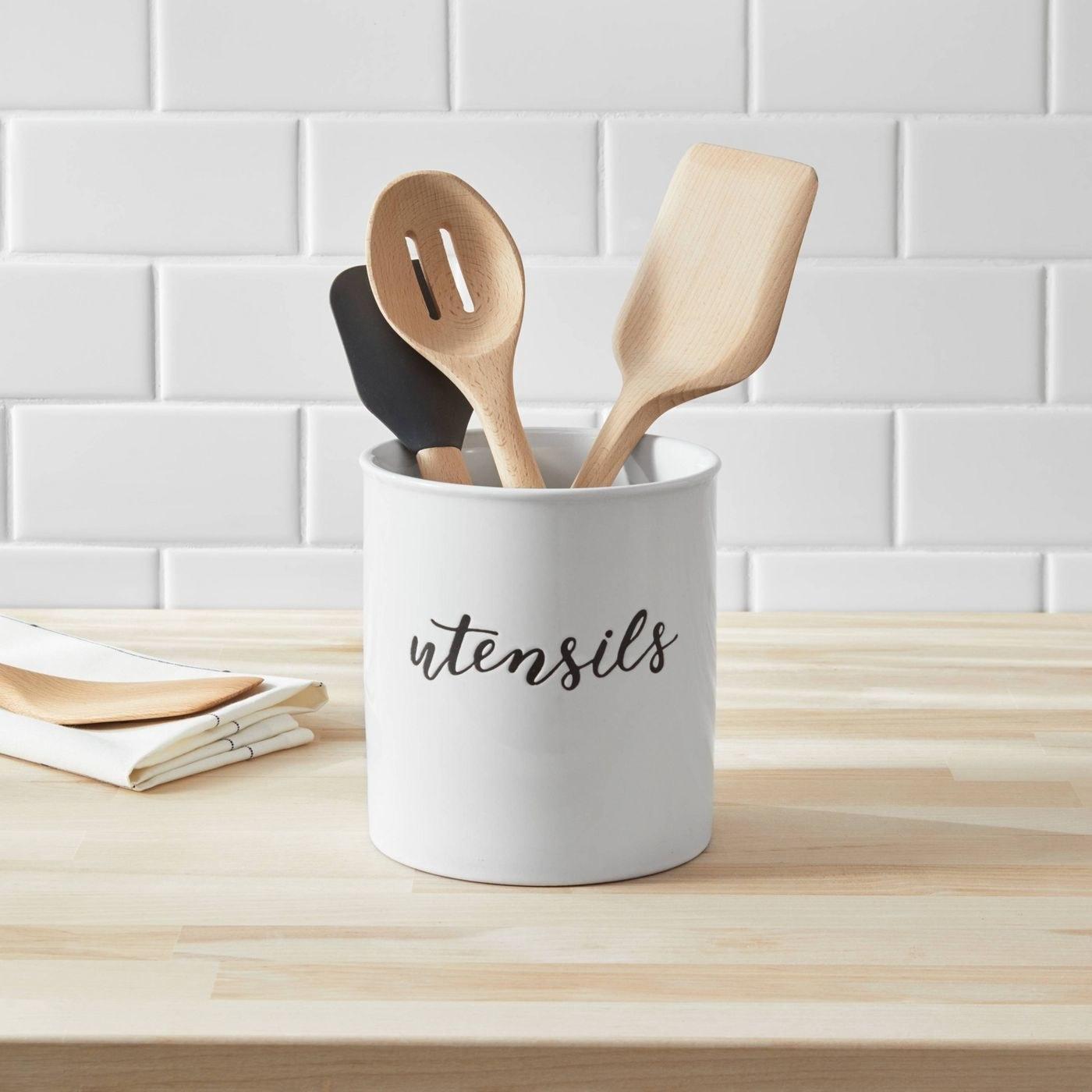 """white utensil holder with """"utensils"""" engraved on the front, holding wooden utensils"""