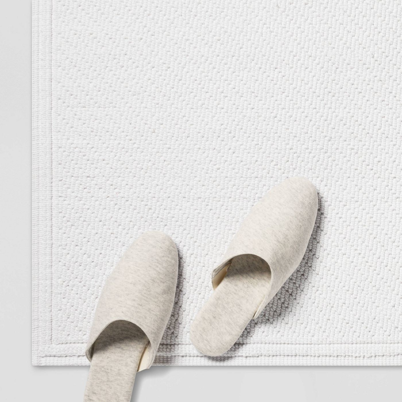 white textured bathmat with pair of white slippers on top