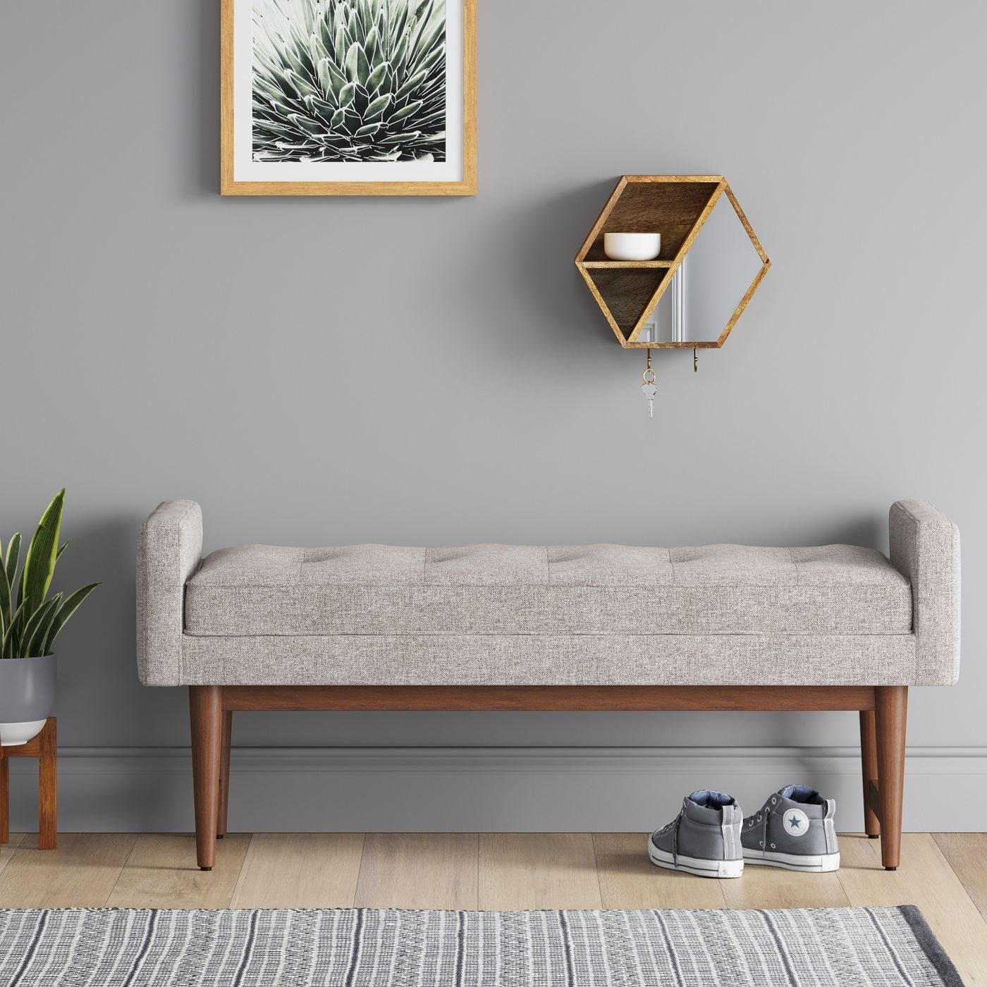grey upholstered bunch with wood legs against a wall