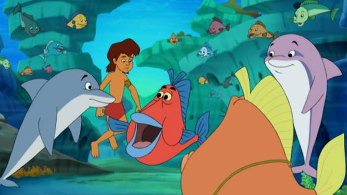A young boy surrounded by sea creatures while underwater, including dolphin and fish
