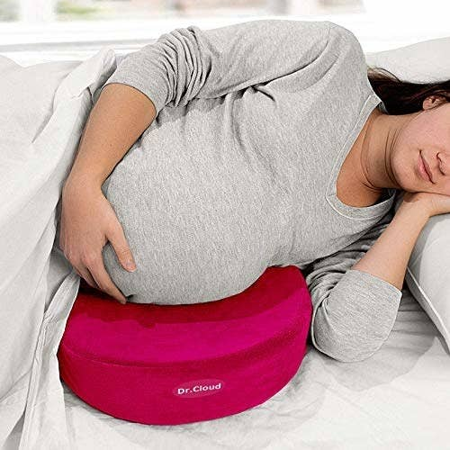 Pregnant women resting her stomach on the maternity pillow and sleeping.