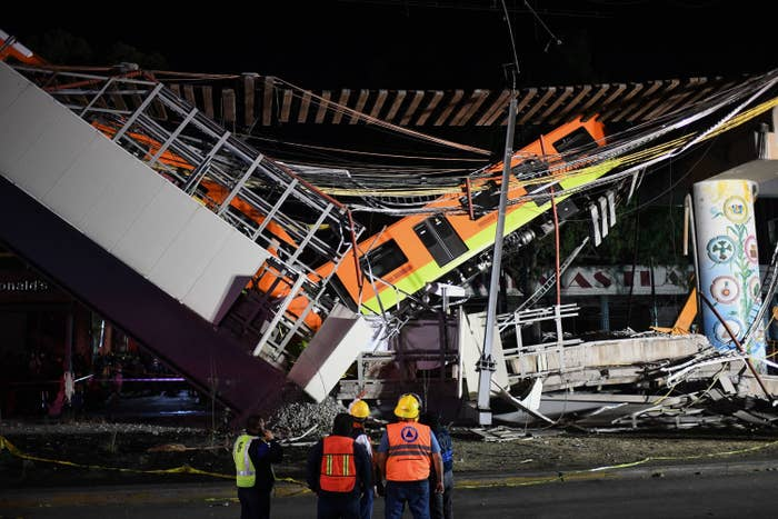 Rescue workers stand in front of the collapsed elevated train under an overpass