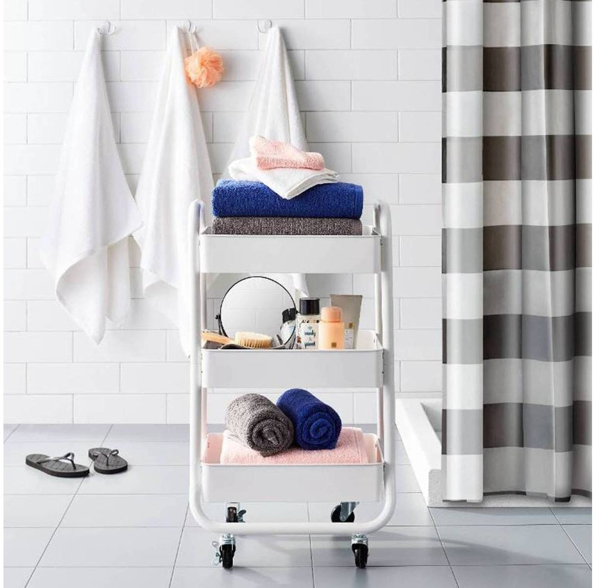 white three-tiered utility cart holding bathroom supplies