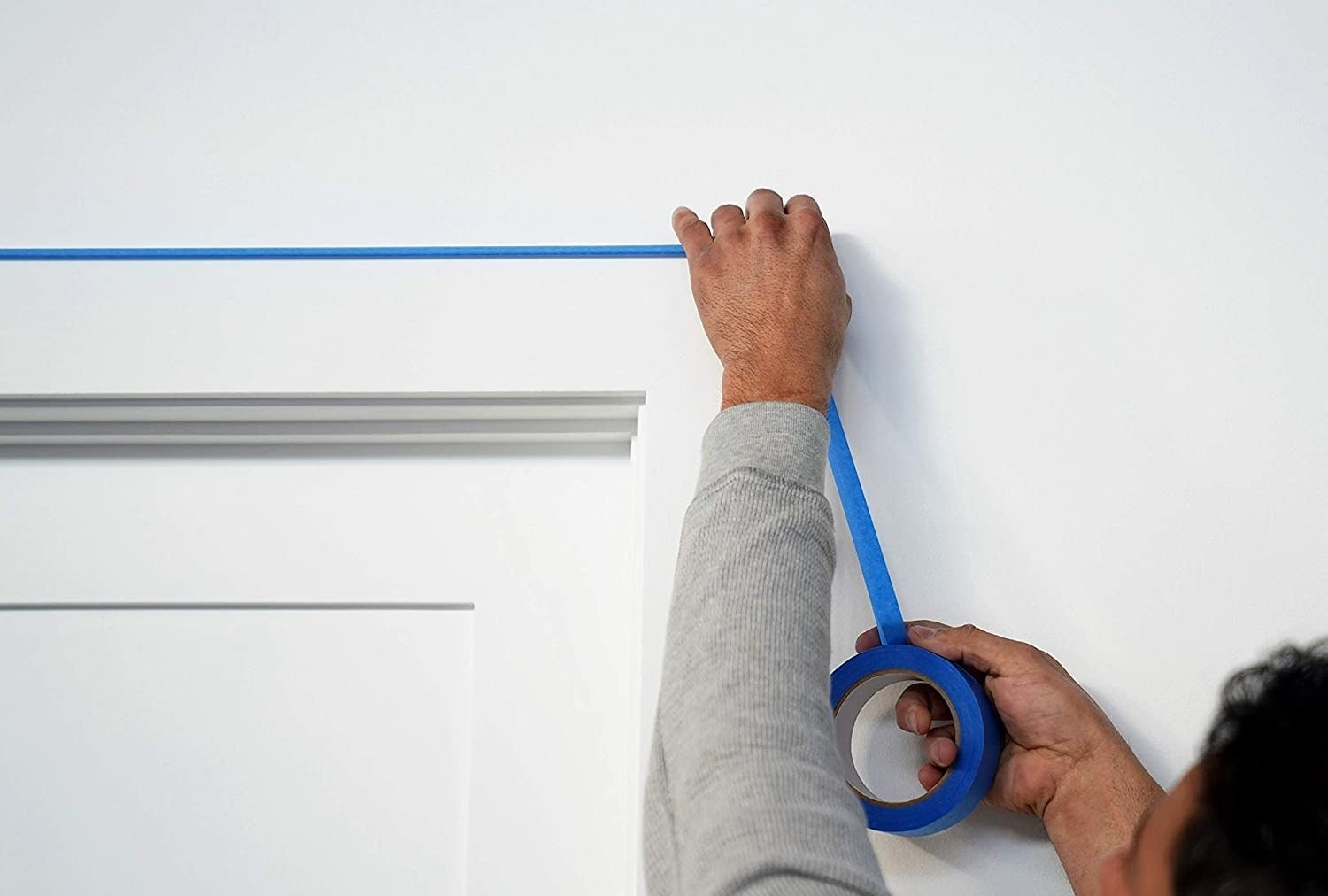 a model sticking the blue tape to a wall