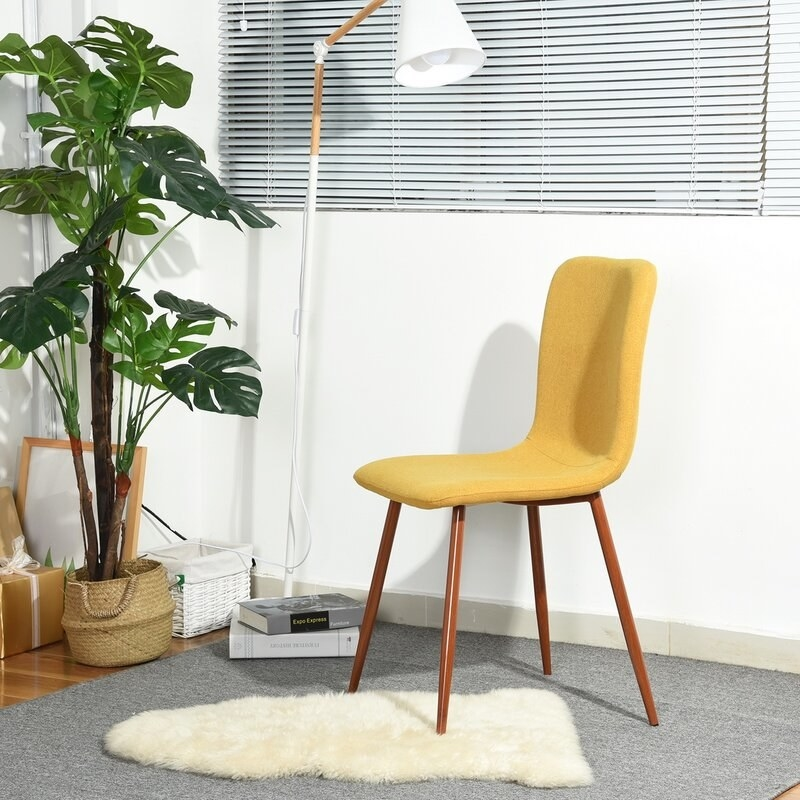 Yellow cloth chair with brown wooden legs