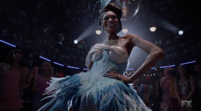 Elektra at a ball wearing a stunning feathered ensemble
