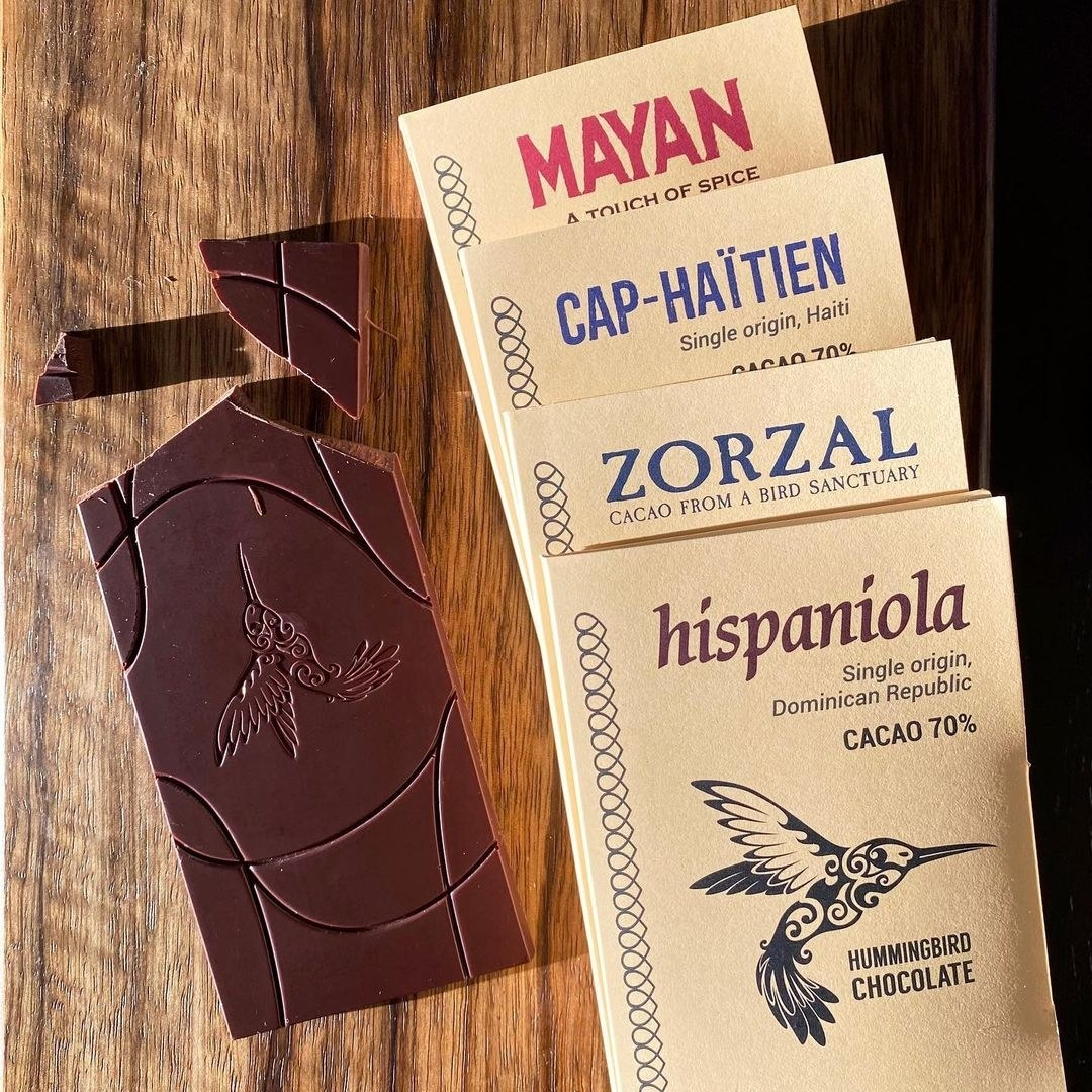 A set of four artisanal chocolate bars on a wooden counter