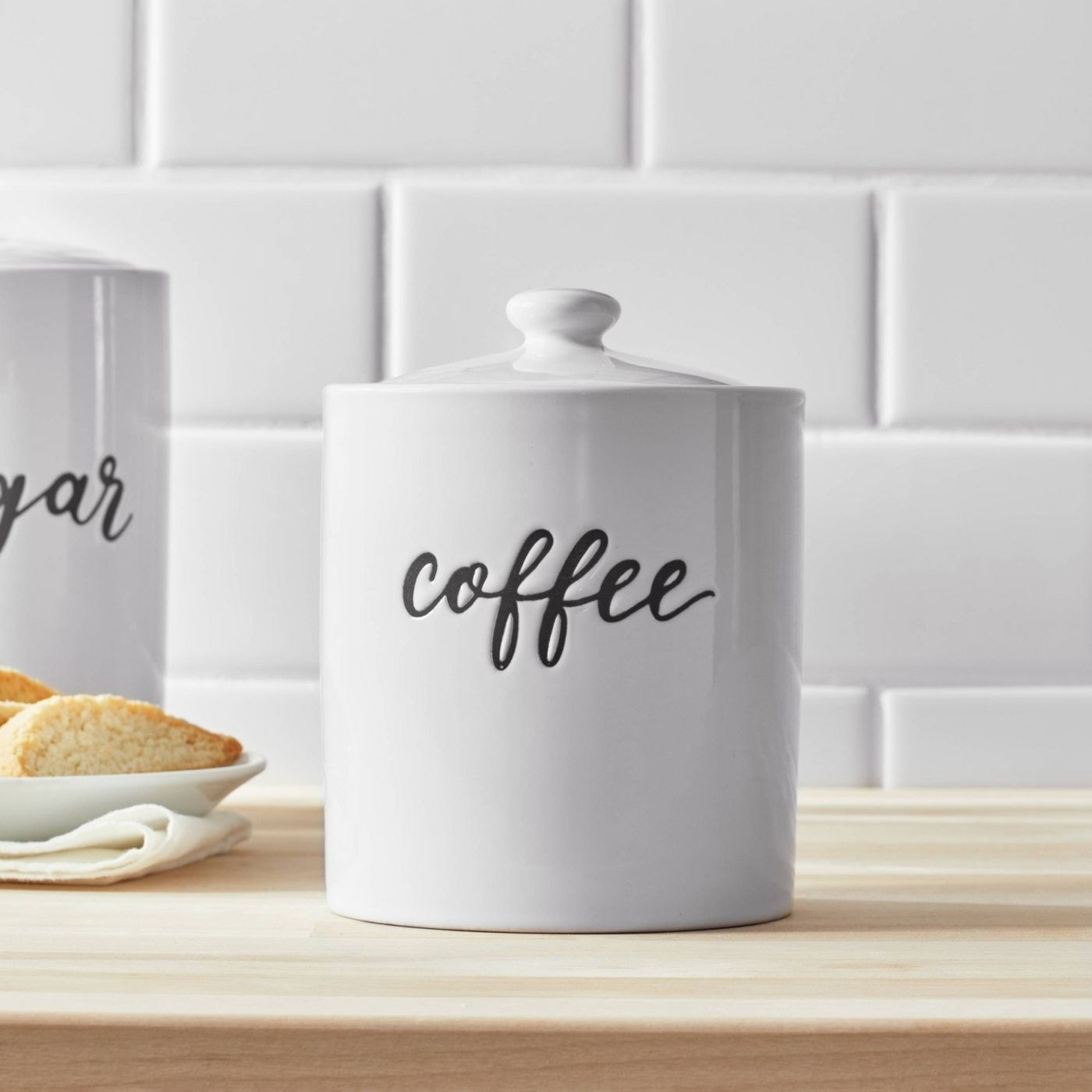 """white coffee storage canister with lid and """"coffee"""" imprinted on the front"""