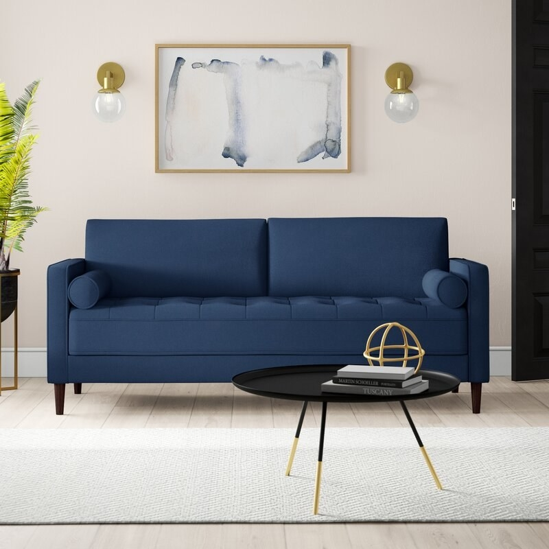 Navy loveseat with tufted design on seating pillows, and cylinder accent pillows