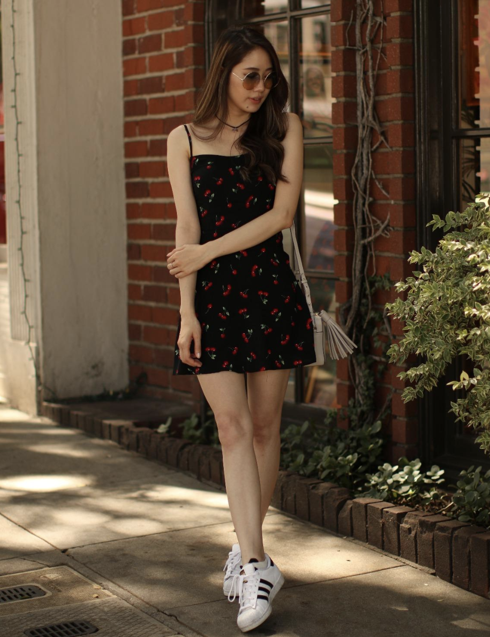 reviewer wearing black mini dress with cherry print