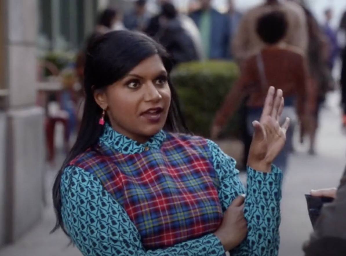 Aggravated Mindy Kaling sticking her hand out in defiance