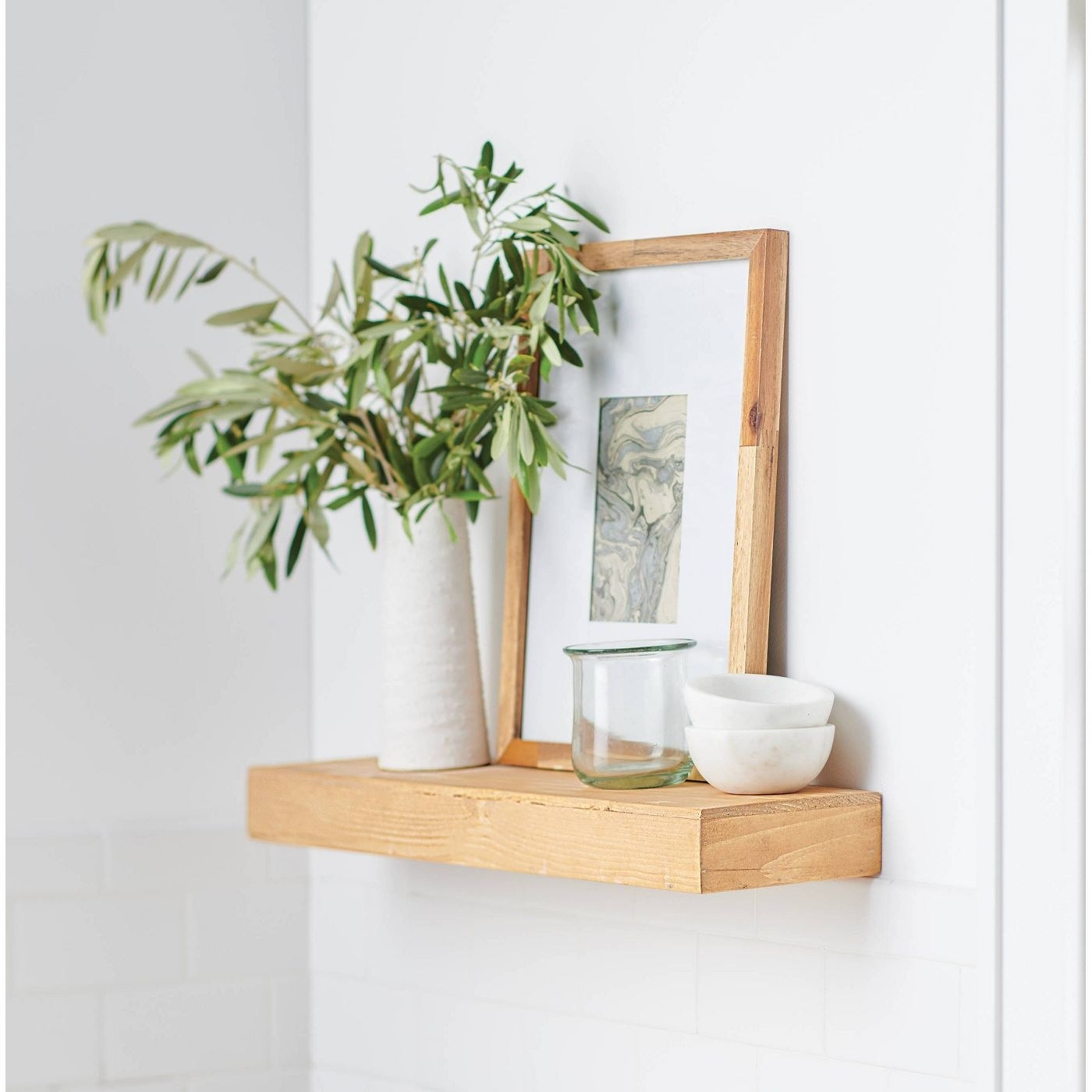 A floating pine wood shelf with photo, plants, and decor on top