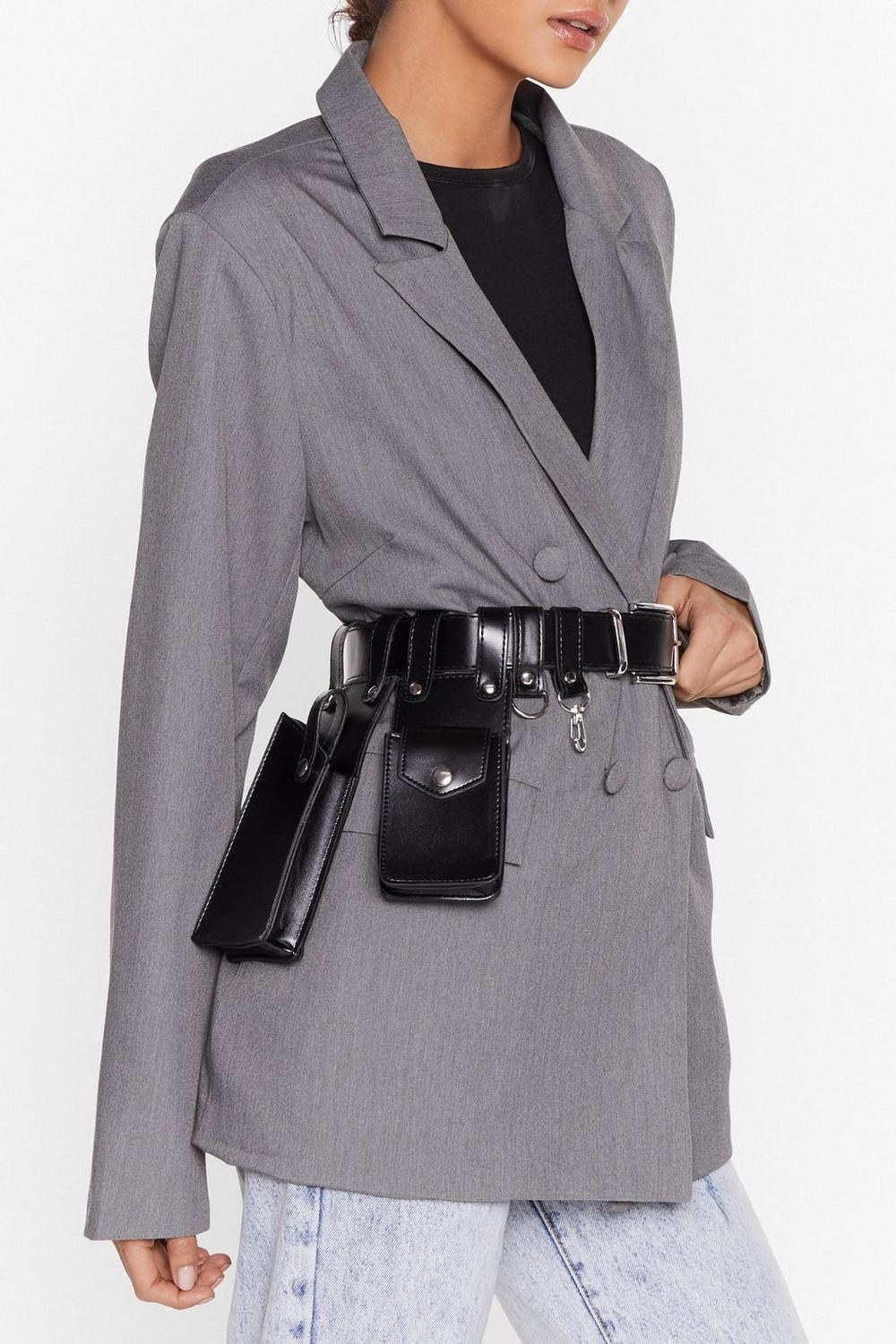 A person wearing the stylish utility belt around their waist over an oversized suit jacket