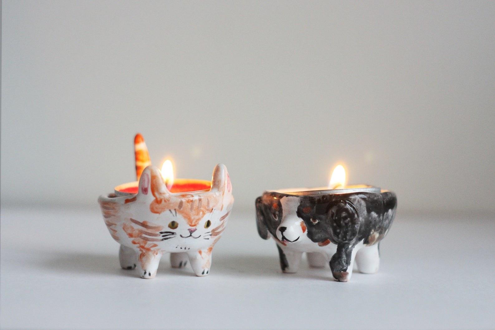 A dog and cat tea light holder with lit tea lights