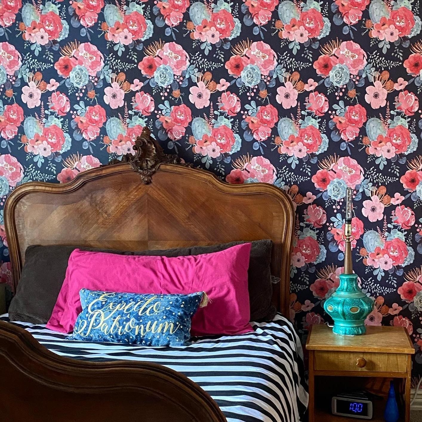 reviewer image of the floral peel and stick wallpaper on a bedroom wall