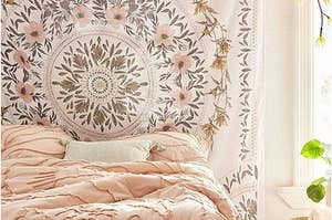 Large white tapestry with pink, green, and brown flowers in leaves in a circular pattern on the tapestry on a wall in a bedroom