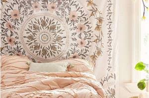 与桃红色,绿色和棕色花的大白色挂毯在叶子的叶子在挂毯的圆形样式在墙壁在卧室