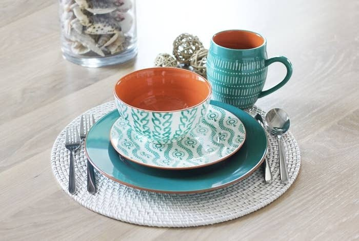 A turquoise 16-piece dinnerware set that contains four dinner plates, four salad plates, four mugs, and four rice bowls