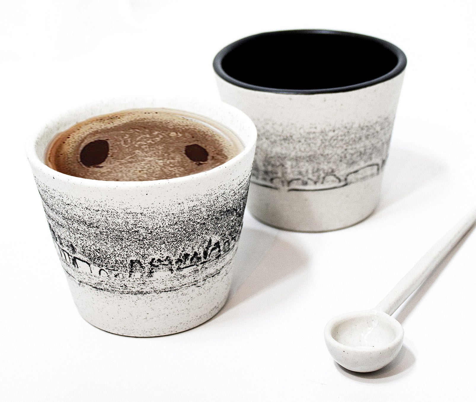 the pair of mugs with one filled with coffee