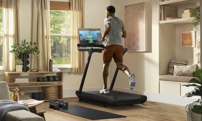 A man runs on a treadmill in a brightly lit living room