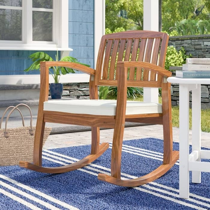 A sturdy, acacia wooden rocking chair that comes with a 100 percent cotton seating cushion
